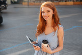 Pretty young girl holding pc tablet and cup of coffee