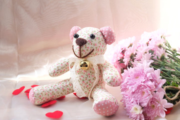 Teddy Bear and dry flower on wooden background.