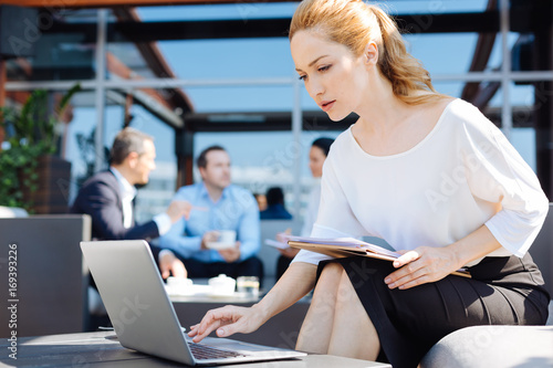 Smart pleasant businesswoman being involved in her work