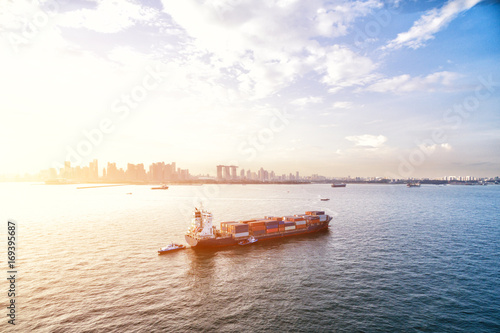 tranquil sea with container ship with sunbeam Poster