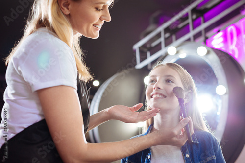 Plakát Smiling woman applying makeup to girls face