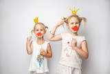 Two cute little girls with paper crown and red lips posing white background at home. - 169407856