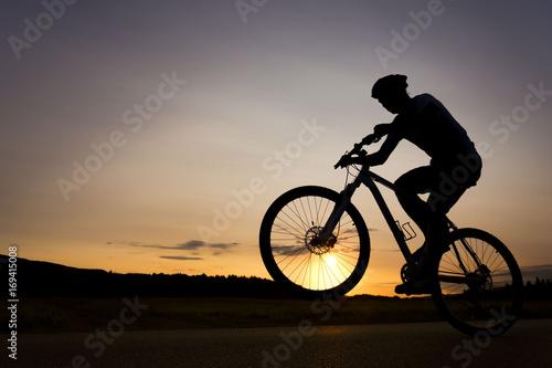 Sylwetka chłopca na rowerze. Młody rowerzysta skacze na rowerze podczas susnet. Koło przednie znajduje się nad horyzontem.