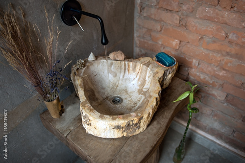 Installation with running water flowing into the stone sink Poster