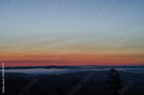 Fotobehang Ochtendgloren Distant lights and fog near the horizon just before sunrise near Heflin, Alabama, USA