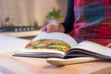 Close-up mid section of a woman, wearing a kitchen apron, reading a recipe book in the kitchen at home.  - 169425030