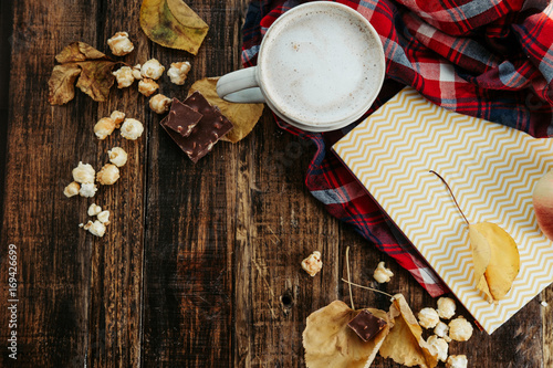 Aluminium Chocolade Hot cocoa (coffee) with popcorn, apple, cakes, leaves on the old wooden boards. Cozy, autumn concept