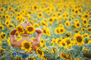 A girl standing with her back against a field of sunflowers in a straw hat. Beautiful tanned hands, healthy sports lifestyle.