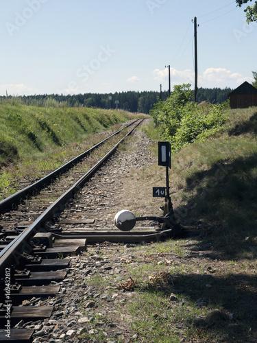 Papiers peints Voies ferrées Small train station on narrow-gauge. Sunshine weather, village train stop. Railroad tracks, railway traffic signs, railroad switch, point.