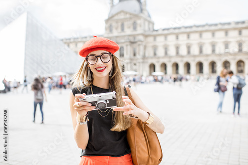 Young woman tourist in red cap walking with photo camera near the famous Louvre Poster