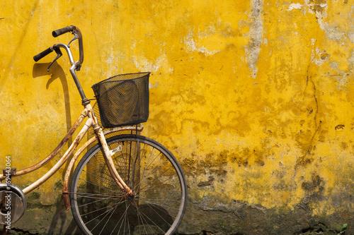 Stary bicykl przeciw starej kolor żółty ścianie na ulicie Hanoi stary miasteczko, Wietnam.