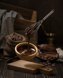 Dark still life with melted chocolate in wooden bowl