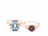 two gold rings with blue topaz and garnets