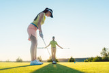 Low-angle side view of an attractive fit woman exercising hitting technique during golf class with an experienced professional player in summer