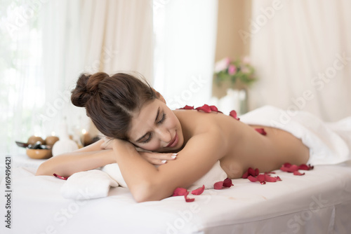 Fototapeta Beautiful smiling woman with flowers resting in the spa before massage.