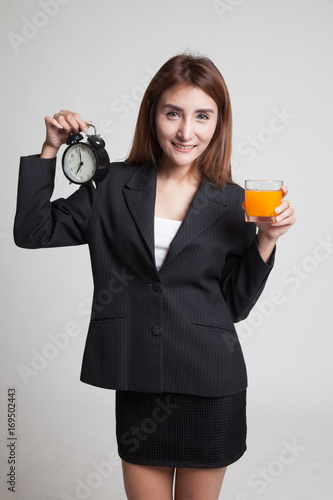 Asian woman with a clock drink orange juice. Poster