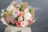 Bouquet in kraft paper. A simple bouquet of flowers and greens - 169521833