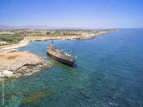 Papiers peints Naufrage Aerial view of abandoned ship wreck EDRO III in Pegeia, Paphos, Cyprus. The rusty shipwreck is stranded on Peyia rocks at kantarkastoi sea caves, Coral Bay, Pafos, standing at an angle near the shore.