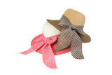 Woven hat with pink, beige and brown, decorated with a pink bow tie, isolated on white background.