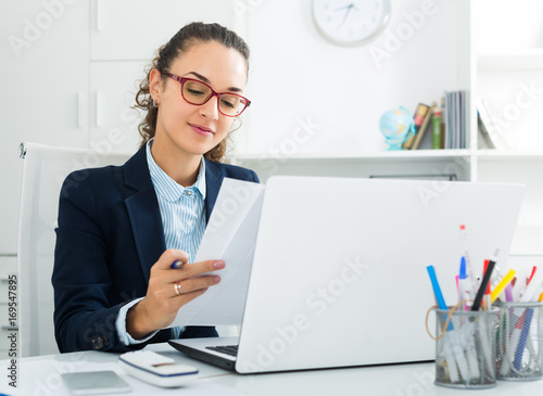 Young woman working with paperwork and laptop