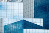 Fototapety Blue sky and clouds reflecting in windows of modern office building