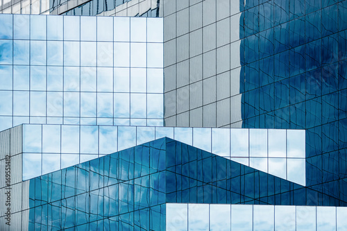 Foto Murales Blue sky and clouds reflecting in windows of modern office building