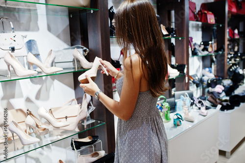 Poster Portrait of a woman in grey dress selecting a pair of female shoes in the shop