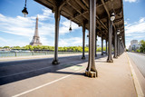 Cityscape view on the old iron bridge with Eiffel tower on the background during the sunny day in Paris