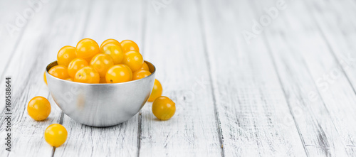 Yellow Tomatoes on wooden background; selective focus