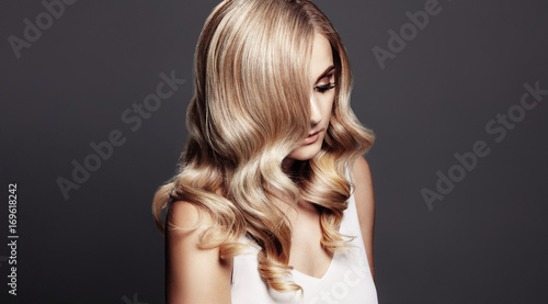Fotobehang Kapsalon Elegant woman with shiny wavy blond hair