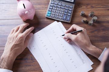 businessman hand calculator,document and piggy bank