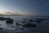 Calms sea around rocks at sunset