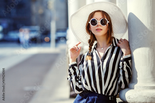 a294837d3c6 Outdoor portrait of young beautiful girl posing in street. Model wearing  stylish sunglasses