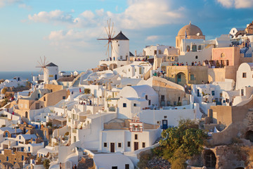 SANTORINI, GREECE - OCTOBER 4, 2015: The look to part of Oia with the windmills in evening light.