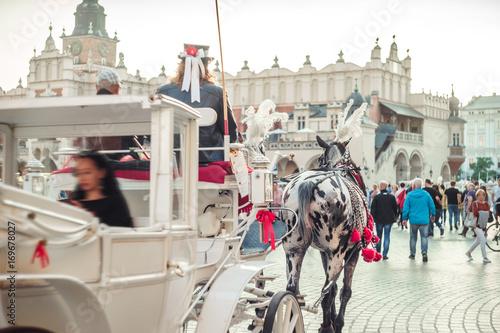 Papiers peints Cracovie White carriage with tourist on market square in Krakow, Poland