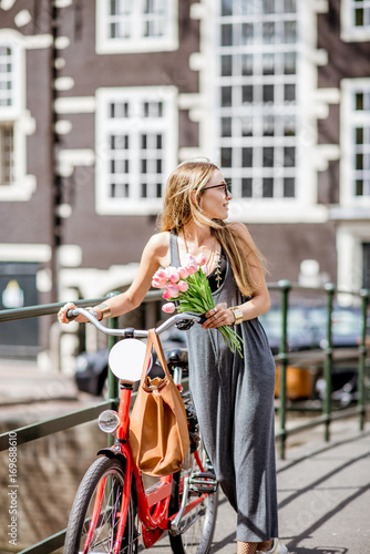 Foto op Plexiglas Amsterdam Young beautiful woman walking with red bicycle and bouguet of tulips on the bridge over the water channel in Amsterdam old city