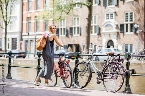 Foto op Plexiglas Amsterdam Young and beautiful woman with bag and flowers walking with bicycle on the water channel in Amsterdam city