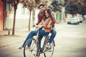 Young couple riding bicycle at the street on autumn day.They sitting on bike and making fun.