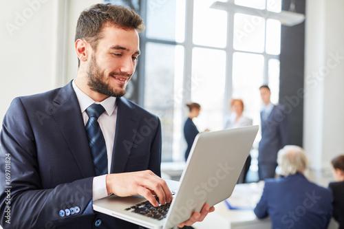 Geschäftsmann mit Laptop Computer online