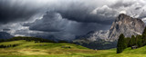 Storm over the mountains Dolomiti in the summer season with meadow in foreground  - 169702027