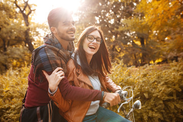 Young couple sitting on bicycle at the park on autumn day.Love and making fun.