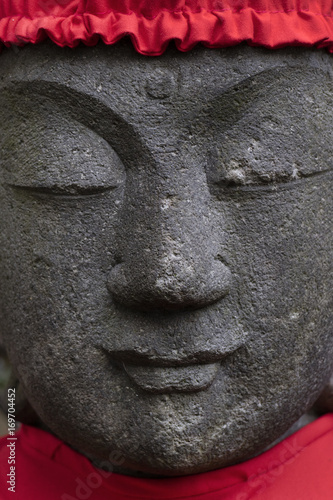 Tokyo, Japan, Buddhist stone statue wearing a red hat Poster