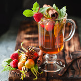 Rosehip tea in glass on black stone background - 169726481