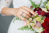 Bride holding bouquet of flowers with dark red silk ribbon close up