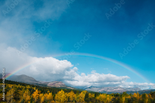 Papiers peints Bleu jean Rainbow over colorful fall tree landscape with clouds