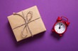 Red alarm clock and gift on purple background
