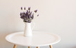Purple lavender in small white jug on round table against neutral wall
