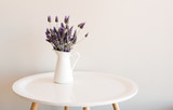 Purple lavender in small white jug on round table against neutral wall - 169758024