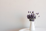 Purple lavender in small white jug on edge of round table against neutral wall with copy space to left - 169758055