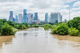 Fototapety High and fast water rising in Bayou River with downtown Houston in background under cloud blue sky. Heavy rains from Harvey Tropical Hurricane storm caused many flooded areas in greater Houston area.